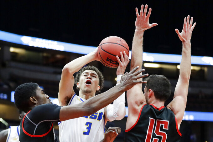 UC Santa Barbara guard JaQuori McLaughlin shoots between Cal State Northridge forward Ron Artest III, left, and guard Cameron Gottfried during the first half of a NCAA college basketball game at the Big West Conference tournament in Anaheim, Calif., Thursday, March 14, 2019. (AP Photo/Chris Carlson)