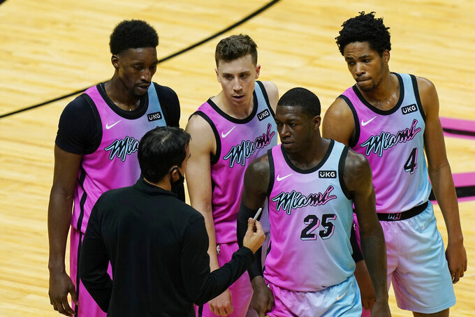 Miami Heat head coach Erik Spoelstra talks to center Bam Adebayo, left, guard Duncan Robinson, guard Kendrick Nunn (25) and forward KZ Okpala (4) during the last minutes of the second half of an NBA basketball game against the Los Angeles Clippers, Thursday, Jan. 28, 2021, in Miami. The Los Angeles Clippers defeated the Heat 109-105. (AP Photo/Marta Lavandier)