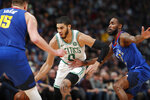 Boston Celtics forward Jayson Tatum, center, drives to the basket between Denver Nuggets center Nikola Jokic, left, and guard Will Barton during the second half of an NBA basketball game Friday, Nov. 22, 2019, in Denver. The Nuggets won 96-92. (AP Photo/David Zalubowski)