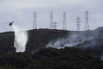 FILE - In this Oct. 10, 2019, file photo, a helicopter drops water near power lines and electrical towers while working at a fire on San Bruno Mountain near Brisbane, Calif. Pacific Gas & Electric plans to bury 10,000 miles of its power lines in an effort to prevent its fraying grid from sparking wildfires when electrical equipment collides with millions of trees and other vegetation sprawling across its drought-stricken service. (AP Photo/Jeff Chiu, File)