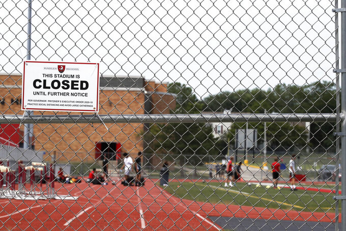 An information sign is displayed at Mundelein high school stadium in Mundelein, Ill., Thursday, July 30, 2020. The Illinois High School Association (IHSA) board of directors voted on Wednesday to move the football, girls volleyball and boys soccer seasons to spring, while making season adjustments to all sports for the 2020-21 school year. All other fall sports such as boys and girls golf, boys and girls cross country, girls swimming and girls tennis will be played as scheduled, with restrictions, according to the IHSA. (AP Photo/Nam Y. Huh)