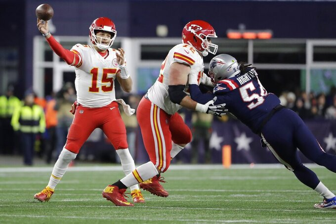 Kansas City Chiefs quarterback Patrick Mahomes. left, passes under pressure from New England Patriots linebacker Dont'a Hightower, right, in the first half of an NFL football game, Sunday, Dec. 8, 2019, in Foxborough, Mass. (AP Photo/Steven Senne)