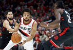 Portland Trail Blazers forward Skal Labissiere, center, dribbles around Toronto Raptors forward Chris Boucher, right, during the first half of an NBA basketball game in Portland, Ore., Wednesday, Nov. 13, 2019. (AP Photo/Craig Mitchelldyer)