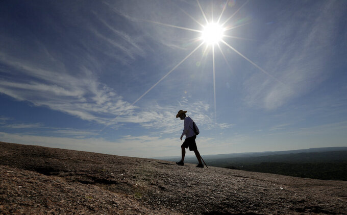 Following social distancing rules and wearing a mask, Thomas Holstad hikes through Enchanted Rock State Park, Monday, April 20, 2020, in Fredericksburg, Texas. Texas state parks are reopened to the public Monday after they had been closed due to the COVID-19 pandemic, but visitors must follow social distancing rules and wear a facial covering or mask. (AP Photo/Eric Gay)