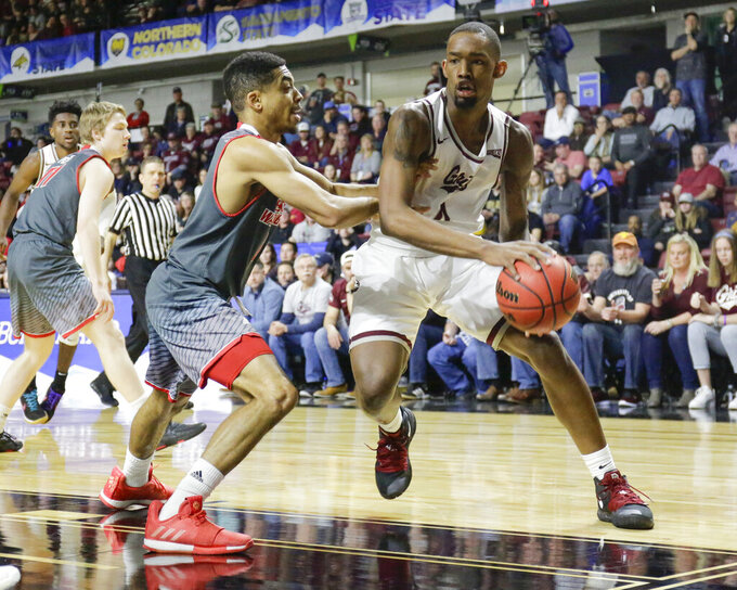 Montana's Sayeed Pridgett (4) moves the ball around Eastern Washington's Tyler Kidd during an NCAA college basketball game in the championship of the Big Sky Tournament in Boise, Idaho, Saturday, March 16, 2019. Montana won 68-62. (AP Photo/Otto Kitsinger)