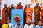 In this May 5, 2019, photo, Buddhist monk and anti-Muslim community leader Wirathu, center, speaks during a nationalist rally in Yangon, Myanmar. A court issued Wednesday, May 29, 2019, an arrest warrant for the Buddhist monk famous for his incendiary comments about the country's Muslim minority and criticisms of the government. The warrant issued in Yangon charges Wirathu with sedition for remarks he made on May 5 about the government of Myanmar's leader, Aung San Suu Kyi. (AP Photo/Aung Naing Soe)