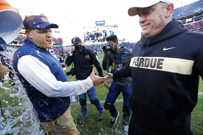Auburn head coach Gus Malzahn, left, gets water poured on him as he shakes hands with Purdue head coach Jeff Brohm after the Music City Bowl NCAA college football game Friday, Dec. 28, 2018, in Nashville, Tenn. Auburn won 63-14. (AP Photo/Mark Humphrey)