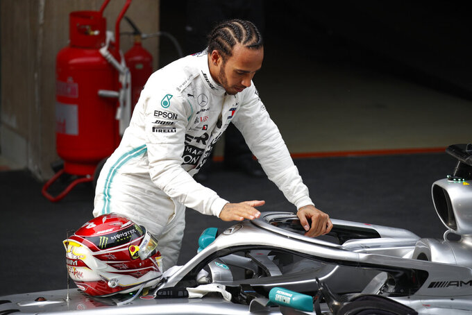 Mercedes driver Lewis Hamilton of Britain touches his car after winning the Chinese Formula One Grand Prix at the Shanghai International Circuit in Shanghai on Sunday, April 14, 2019. Vettel finished third. (AP Photo/Andy Wong)
