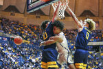 West Virginia's Jermaine Haley (10) and Taz Sherman (11) become entangled with Akron's Greg Tribble during the second half of an NCAA college basketball game, Friday, Nov. 8, 2019, in Morgantown, W.Va. (AP Photo/Kathleen Batten)