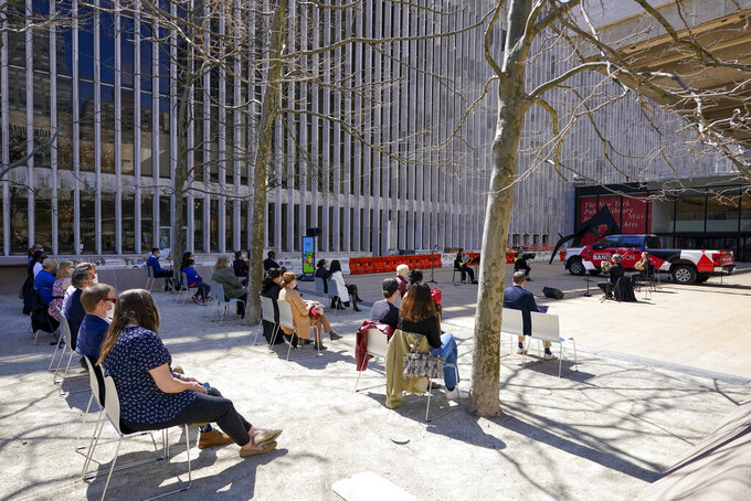 Members of the New York Philharmonic perform on the Lincoln Center campus as part of Restart Stages at Lincoln Center, Wednesday, April 7, 2021, in New York. Members of the New York Philharmonic gave an outdoor concert at Lincoln Center for heath care workers, 13 months after the novel coronavirus pandemic decimated their season. (AP Photo/Mary Altaffer)