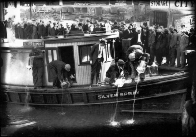 FILE - In this 1922 file photo spectators gather by the side of captured rum runner, Silver Spray, as they watch prohibition agents pour