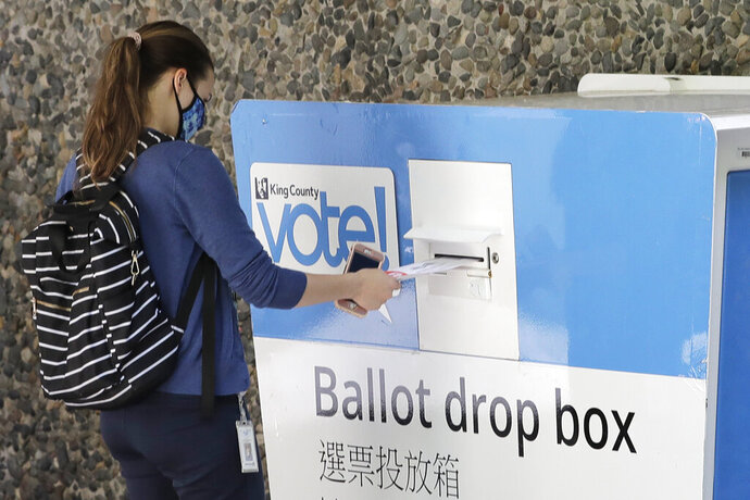 A person drops off a ballot for Washington state's primary election, Tuesday, Aug. 4, 2020, at a collection box at the King County Administration Building in Seattle. Voters in the state have the option of voting by mail, depositing ballots in boxes, or seeking help in person for a missing ballot or other issues. (AP Photo/Ted S. Warren)