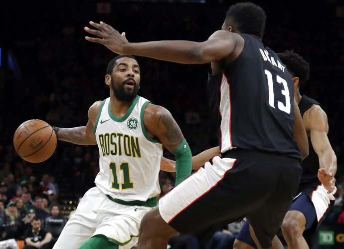 Boston Celtics guard Kyrie Irving (11) makes a move against Washington Wizards center Thomas Bryant (13) during the first quarter of an NBA basketball game Friday, March 1, 2019, in Boston. (AP Photo/Elise Amendola)
