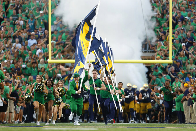 FILE - In this Sept. 1, 2018, file photo, a Notre Dame leprechaun mascot leads the team onto the field before an NCAA football game against Michigan in South Bend, Ind. In 2021, college football will attempt to return to normal after a season roiled by the pandemic while also adapting to a new paradigm in which the athletes have more power than ever before. (AP Photo/Paul Sancya, File)
