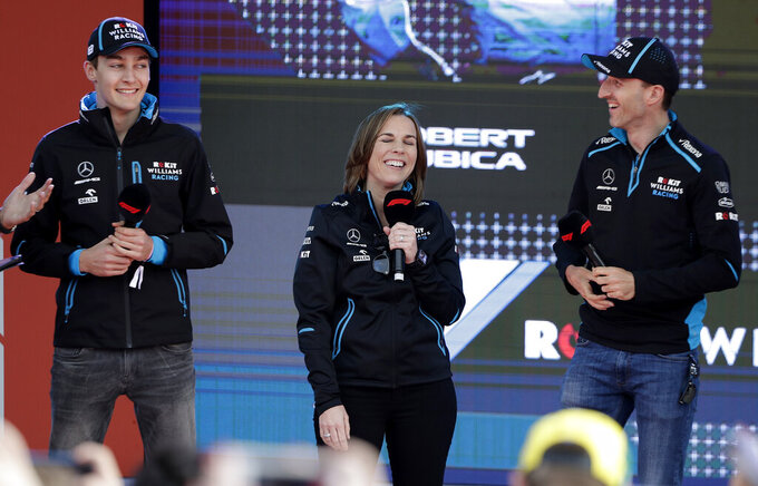 Williams driver Robert Kubica of Poland, right, and teammate George Russell of Britain, laugh with team principal Williams team principal Claire Williams during the launch for the Australian Grand Prix in Melbourne, Australia, Wednesday, March 13, 2019. (AP Photo/Rick Rycroft)