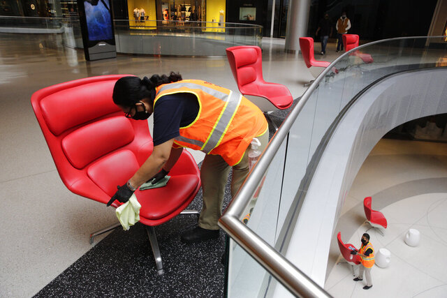 Cleaning crew members, Rosalinda Venado, top, cleans and disinfects the center throughout the day, and after-hours, with a focus on high-touch, high-traffic surfaces while using a strong disinfectant at the Beverly Center shopping mall in Los Angeles Friday, May 29, 2020. (AP Photo/Damian Dovarganes)