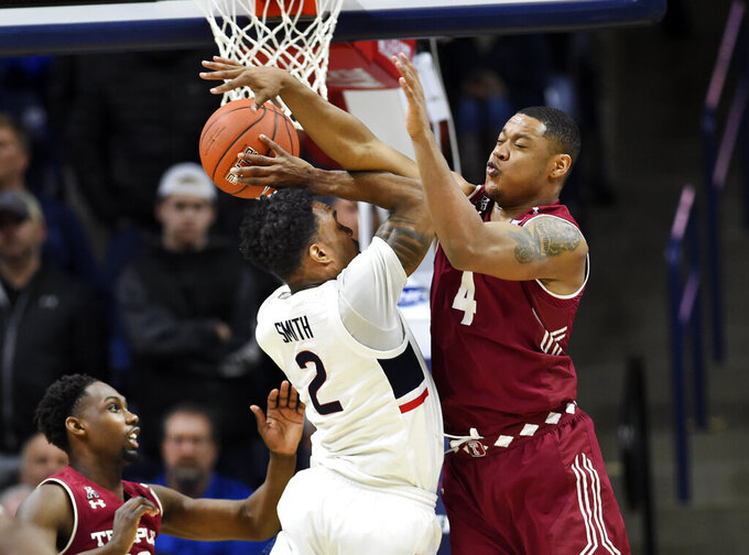 Connecticut's Tarin Smith (2) is defended by Temple's J.P. Moorman II (4) in the second half of an NCAA college basketball game, Thursday, March 7, 2019, in Storrs, Conn. (AP Photo/Stephen Dunn)
