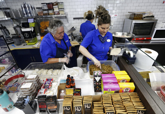In this Tuesday, Aug. 14, 2018 photo, Emma Gonzalez, left, and Lidices Ramos, right, make empanadas at the Mendez Fuel convenience store in Miami. There's no stale doughnuts and cold coffee at Mendez Fuel convenience store in Miami. Instead, customers can get their caffeine fix with an iced matcha and grab some vegan empanadas or an acai bowl for the road. (AP Photo/Lynne Sladky)