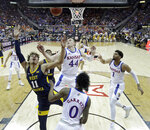 West Virginia's Emmitt Matthews Jr. (11) gets past Kansas' Mitch Lightfoot (44) to put up a shot during the first half of an NCAA college basketball game in the Big 12 men's tournament Friday, March 15, 2019, in Kansas City, Mo. (AP Photo/Charlie Riedel)