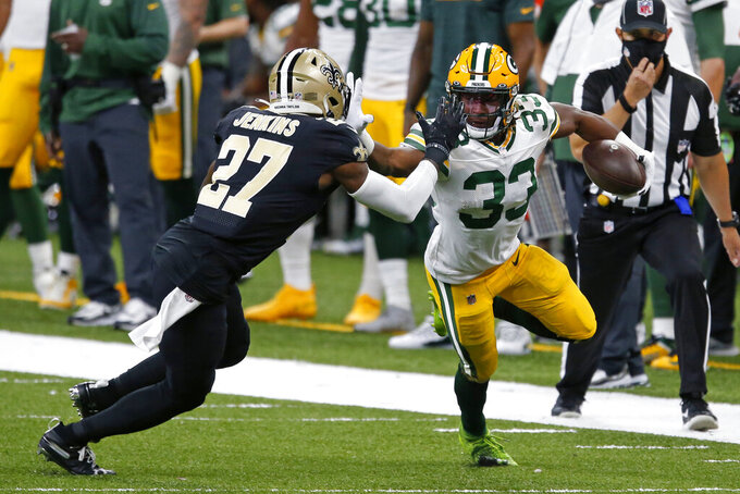 Green Bay Packers running back Aaron Jones (33) carries against New Orleans Saints strong safety Malcolm Jenkins (27) in the first half of an NFL football game in New Orleans, Sunday, Sept. 27, 2020. (AP Photo/Butch Dill)