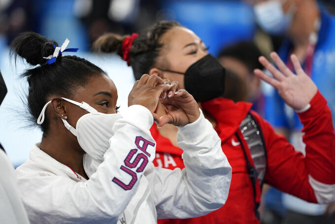 Simone Biles, of the United States, and teammates Sunisa Lee wave after performing on the balance beam during the artistic gymnastics women's apparatus final at the 2020 Summer Olympics, Tuesday, Aug. 3, 2021, in Tokyo, Japan. (AP Photo/Ashley Landis)