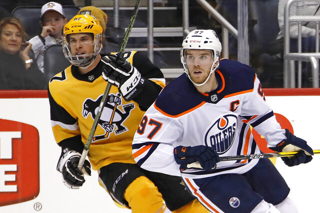 FILE - In this Nov. 2, 2019, file photo, Edmonton Oilers' Connor McDavid (97) and Pittsburgh Penguins' Sidney Crosby (87) skate during the second period of an NHL hockey game in Pittsburgh. Edmonton Oilers captain Connor McDavid is still regarded as the NHL's top forward, while peers consider Pittsburgh's Sidney Crosby the game's most complete player, according to the NHL Players' Association's annual poll of players released Tuesday, March 31, 2020. (AP Photo/Gene J. Puskar, File)