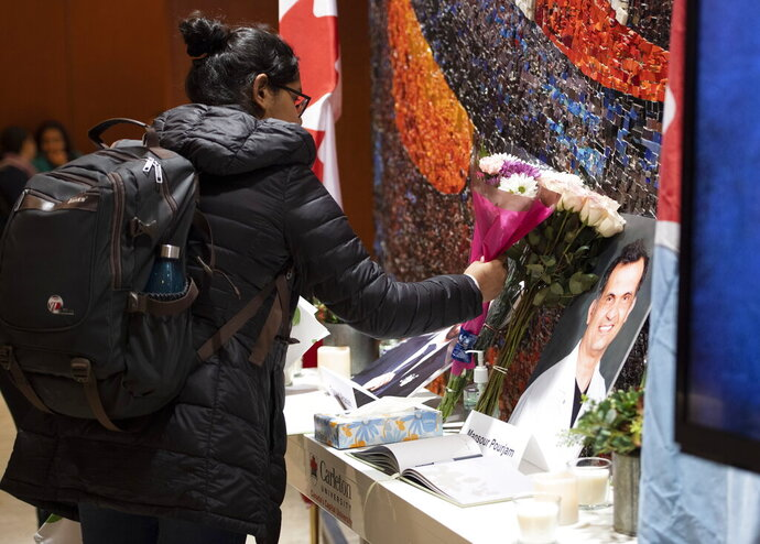 Flowers are laid beside books of condolence before ceremony at Carleton University Wednesday, Jan. 15, 2020 to honor biology PhD student Fareed Arastech and biology alumnus Mansour Pourjam, who died in the crash of Ukraine International Airlines Flight PS752 in Tehran. (Justin Tang/The Canadian Press via AP)