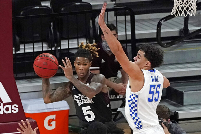 Mississippi State guard Deivon Smith (5) passes out a rebound as Kentucky forward Lance Ware (55) defends during the second half of an NCAA college basketball game in Starkville, Miss., Saturday, Jan. 2, 2021. Kentucky won 78-73. (AP Photo/Rogelio V. Solis)