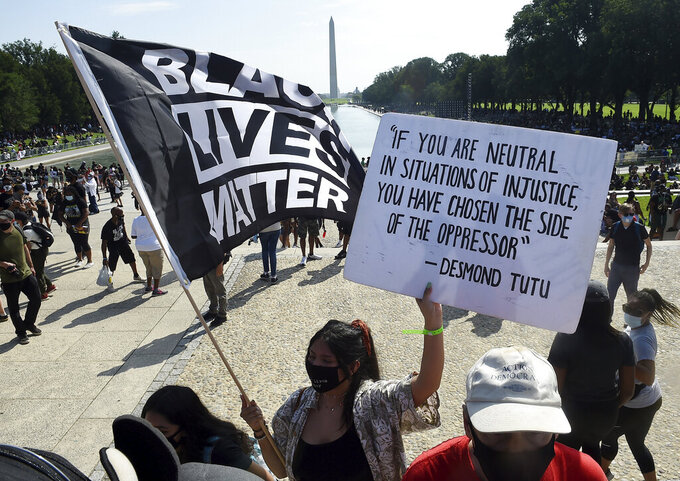 """FILE - In this Aug. 28, 2020, file photo, demonstrators gather near the Lincoln Memorial as final preparations are made for the March on Washington, in Washington, on the 57th anniversary of the Rev. Martin Luther King Jr.'s """"I Have A Dream"""" speech. Several years since its founding, BLM has evolved well beyond the initial aspirations of its early supporters. Now, its influence faces a test, as voters in the Tuesday, Nov. 3 general election choose or reject candidates who endorsed or denounced the BLM movement amid a national reckoning on race (Olivier Douliery/Pool Photo via AP, File)"""