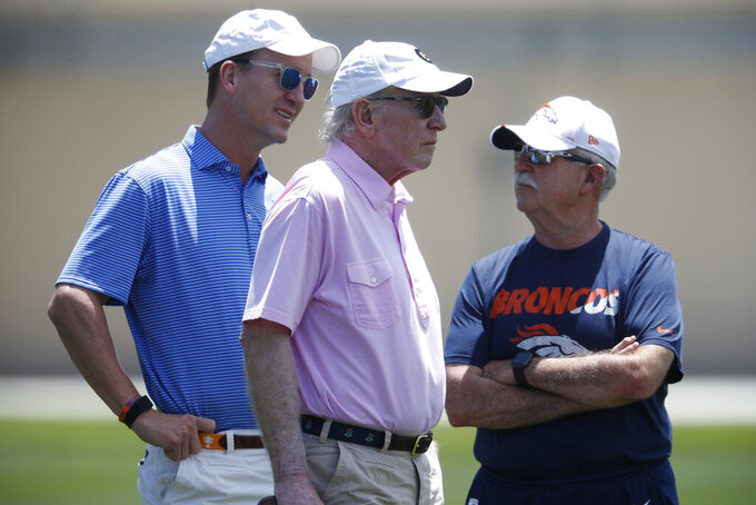 Former NFL quarterbacks Peyton Manning, left, and father Archie, center, chat with Denver Broncos head trainer Steve Antonopulos as the Broncos work out at the team's NFL football training facility Wednesday, June 5, 2019, in Englewood, Colo. (AP Photo/David Zalubowski)