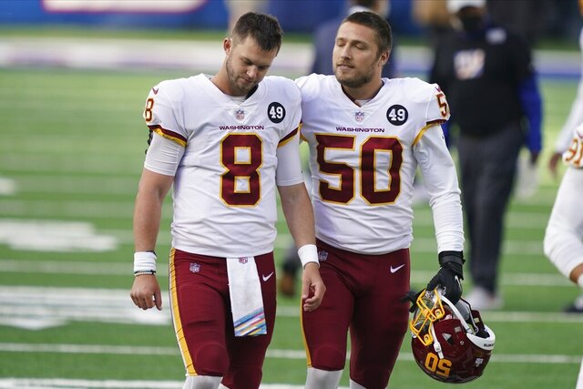 Washington Football Team quarterback Kyle Allen (8) is comforted by Jared Norris (50) after an NFL football game against the New York Giants, Sunday, Oct. 18, 2020, in East Rutherford, N.J. (AP Photo/John Minchillo)