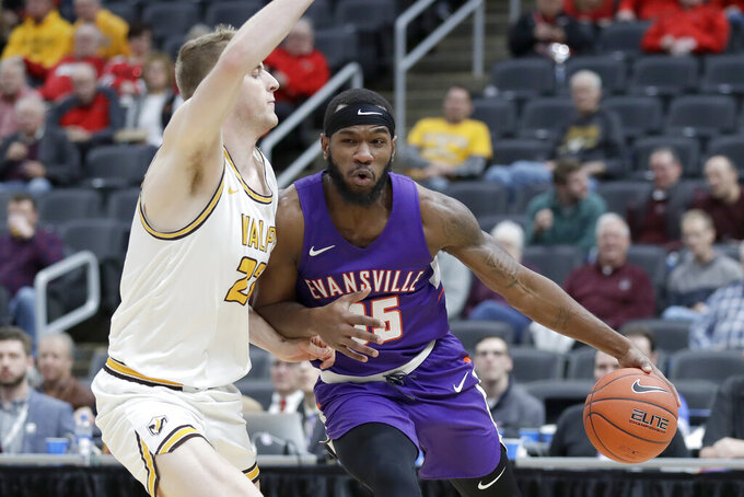 Evansville's John Hall, right, heads to the basket past Valparaiso's Ben Krikke during the first half of an NCAA college basketball game in the first round of the Missouri Valley Conference men's tournament Thursday, March 5, 2020, in St. Louis. (AP Photo/Jeff Roberson)