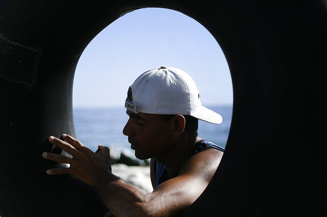 Larry Jimenez, 34, inflates his inner tube in preparation for open sea fishing, at Playa Escondida in La Guaira, Venezuela, Friday, Aug. 14, 2020, amid the new coronavirus pandemic. Venezuelans like Jimenez have turned to fishing the high sea on salvaged inner tubes for survival as the nationwide lockdown paralyzes an already crumbling economy and eliminates their jobs in construction and restaurants. (AP Photo/Matias Delacroix)