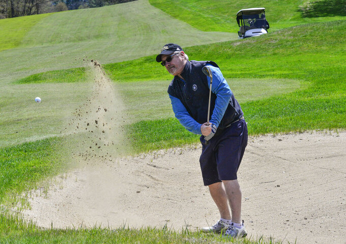 Chris Huffman, of Brattleboro, Vt., chips his ball out of a sand trap while playing golf at the Brattleboro Country Club, Friday, May 8, 2020, in Brattleboro, Vt.. Golfers return to the course after a delayed opening because of the COVID-19 pandemic. (Kristopher Radder/The Brattleboro Reformer via AP)