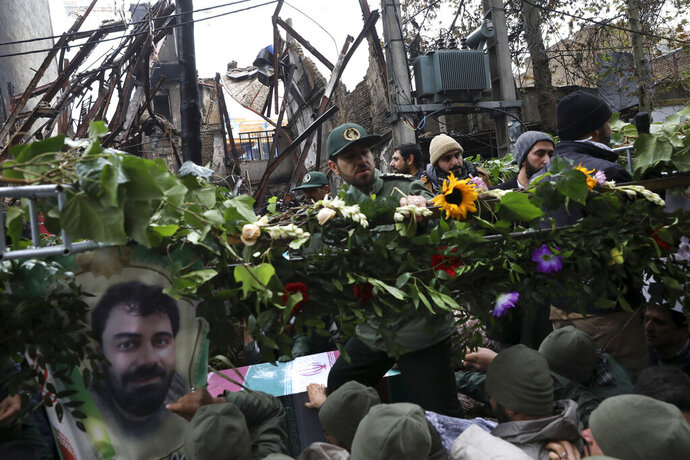 Mourners surround the flag-draped coffin of Revolutionary Guard member Morteza Ebrahimi, seen in a poster at the bottom left, during a funeral procession that passed protest-damaged buildings in the town of Shahriar, Iran, some 40 kilometers (25 miles) southwest of the capital, Tehran, Wednesday, Nov. 20, 2019. Ebrahimi was killed during protests over government-set fuel prices rising last week, demonstrations that quickly spiraled in violence. (AP Photo/Vahid Salemi)