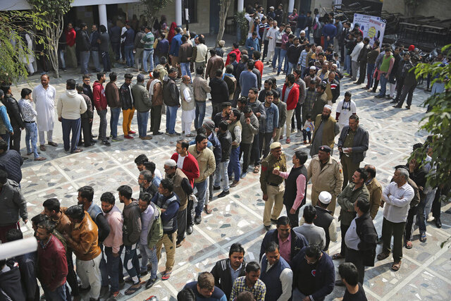 People wait for their turn to cast their vote at a polling station closest to the Shaheen Bagh protest where Muslim women have been protesting for weeks against a new citizenship law, in New Delhi, India, Saturday, Feb. 8, 2020. Voting began for a crucial state election in India's capital on Saturday with Prime Minister Narendra Modi's Hindu nationalist party trying to regain power after a 22-year gap and major victories in a national vote. The BJP campaign has reopened old wounds in the Hindu-Muslim divide and treats the election as a referendum on nearly two months of protests across India against a new citizenship law that excludes Muslims. (AP Photo/Altaf Qadri)