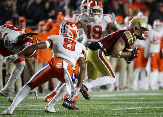 Boston College's Michael Walker, right, runs past Clemson's A.J. Terrell (8) and Tanner Muse (19) as he returns a punt for a touchdown during the first half of an NCAA college football game, Saturday, Nov. 10, 2018, in Boston. (AP Photo/Elise Amendola)