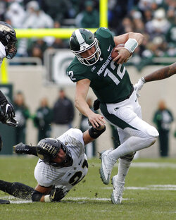 Michigan State quarterback Rocky Lombardi, right, escapes from Purdue's Markus Bailey during the second quarter of an NCAA college football game, Saturday, Oct. 27, 2018, in East Lansing, Mich. (AP Photo/Al Goldis)