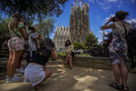 """People take pictures in front of Sagrada Familia Basilica designed by architect Antoni Gaudi in Barcelona, Spain, Friday, July 9, 2021. Spain's top diplomat is pushing back against French cautions over vacationing on the Iberian peninsula. Southern Europe's holiday hotspots worry that repeated changes to rules on who can visit is putting people off travel. On Thursday, France's secretary of state for European affairs, Clement Beaune, advised people to """"avoid Spain and Portugal as destinations"""" when booking their holidays because COVID-19 infections are surging there. (AP Photo/Joan Mateu)"""