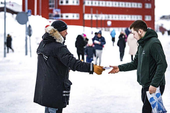 Candidates from the Greenlandic party Siumut pass out flyers in Nuuk in Greenland, Wednesday, March 31, 2021. The autonomous territory within the Kingdom of Denmark, Greenland, will hold election to its Parliament consisting of 31 members, on April 6, 2021. (Emil Helms/Ritzau Scanpix via AP)
