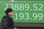 A man walks by an electronic stock board of a securities firm in Tokyo, Tuesday, Jan. 21, 2020. Asian stock markets have tumbled as concern about the impact of a Chinese disease outbreak on tourism and regional economies grows. (AP Photo/Koji Sasahara)