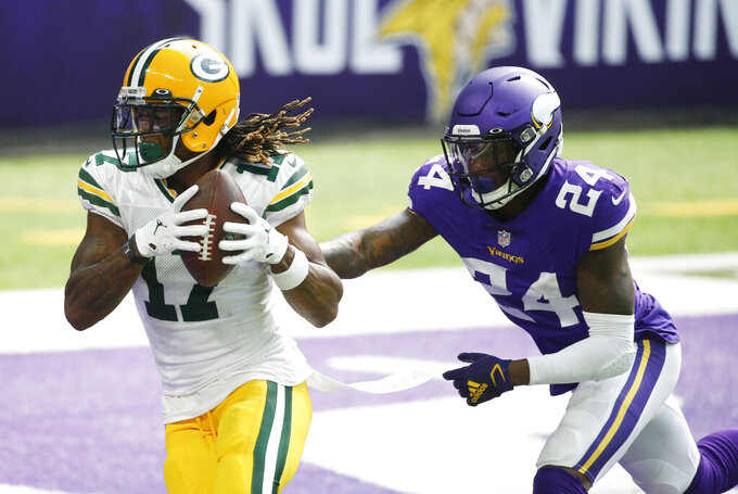 Green Bay Packers wide receiver Davante Adams catches a 1-yard touchdown pass ahead of Minnesota Vikings defensive back Holton Hill, right, during the second half of an NFL football game, Sunday, Sept. 13, 2020, in Minneapolis. (AP Photo/Bruce Kluckhohn)