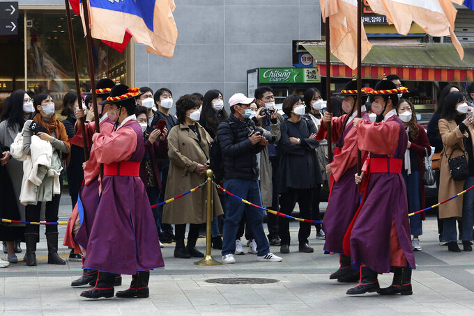 People wearing face masks watch a re-enactment ceremony of the changing of the Royal Guards, in front of the main gate of the Deoksu Palace in Seoul, South Korea, Friday, Nov. 13, 2020. South Korea has reported its biggest daily jump in COVID-19 cases in 70 days as the government began fining people who fail to wear masks in public.(AP Photo/Ahn Young-joon)
