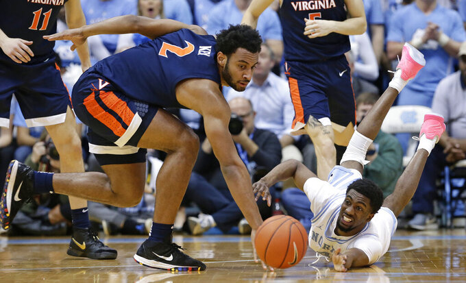 Virginia's Braxton Key, left, and North Carolina's Brandon Robinson, right, chase a loose ball during the second half of an NCAA college basketball game in Chapel Hill, N.C., Monday, Feb. 11, 2019. Virginia won 69-61. (AP Photo/Gerry Broome)