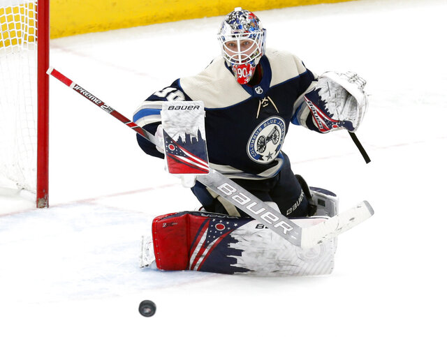 FILE - In this Feb. 10, 2020, file photo, Columbus Blue Jackets goalie Elvis Merzlikins, of Latvia, makes a stop against the Tampa Bay Lightning during an NHL hockey game in Columbus, Ohio.  The Blue Jackets have signed rookie goaltender Merzlikins to a two-year contract worth a reported $8 million. The 26-year-old Latvian became a fan favorite while successfully filling in for an injured Joonas Korpisalo in the second half of the season. (AP Photo/Paul Vernon, File)