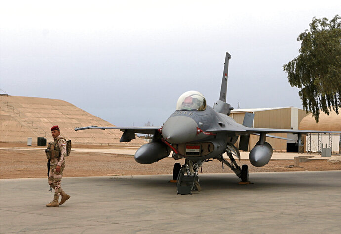 FILE - in this Feb. 13, 2018 file photo, an Iraqi army soldier stand guard near a U.S.- made Iraqi Air Force F-16 fighter jet at the Balad Air Base, Iraq. Iraqi security officials said on Jan. 12, 2020, four members of Iraq's military have been wounded by a rocket attack targeting Balad Air Base, an air base just north of Baghdad. American trainers and a company that services F-16 aircraft are present at that base. Sunday's attack by at least six rockets came just days after Iran fired ballistic missiles at two bases in Iraq housing U.S. forces, causing no casualties. (AP Photo/Khalid Mohammed, File)