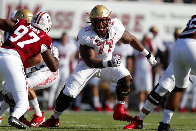 FILE - Boston College offensive lineman Zion Johnson (77) plays against Massachusetts during the first half of an NCAA college football game in Amherst, Mass., in this Saturday, Sept. 11, 2021, file photo. Johnson was selected to The Associated Press Midseason All-America team, announced Tuesday, Oct. 19, 2021. (AP Photo/Michael Dwyer, File)