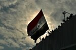 Anti-government protesters wave a flag while standing on a building near Tahrir Square during ongoing protests in Baghdad, Iraq, Sunday, Dec. 1, 2019. Iraq's parliament approved the resignation of Prime Minister Adel Abdul-Mahdi on Sunday, amid ongoing violence and anti-government demonstrations in the capital. (AP Photo/Hadi Mizban)