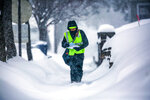 A postal carrier carries mail along First Avenue as snow falls, Tuesday, Feb. 12, 2019, in Wausau, Wis. The latest snow storm to move through the state dropped several inches of snow overnight. (T'xer Zhon Kha/The Post-Crescent via AP)