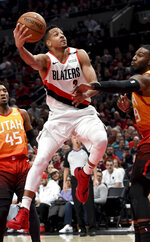 Portland Trail Blazers guard CJ McCollum, center, drives to the basket on Utah Jazz guard Donovan Mitchell, left and forward Jae Crowder, right, during the second half of an NBA basketball game in Portland, Ore., Wednesday, Jan. 30, 2019. (AP Photo/Steve Dykes)